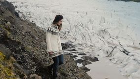 Jonge reizende vrouw die door de rotsen in de bergen lopen, die de Vatnajokull-gletsjerslagune in IJsland onderzoeken stock footage