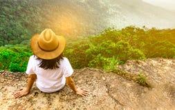 Jonge reizende vrouw die hoed dragen en op de bovenkant van de bergklip zitten met het ontspannen van stemming en het letten van  stock foto's