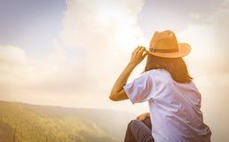 Jonge reizende vrouw die hoed dragen en op de bovenkant van de bergklip zitten met het ontspannen van stemming en het letten van  stock afbeelding