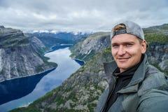 Jonge reiziger die selfie op de bovenkant met Mooie fjord op achtergrond in Noorwegen nemen royalty-vrije stock afbeeldingen