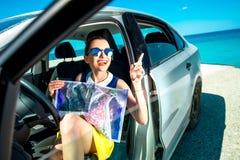 Jonge reiziger met kaartzitting in de auto Stock Fotografie