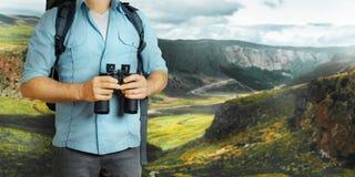 Jonge Reizigersmens met Rugzak en Verrekijkers die naar Richting in Bergen streven De Reisconcept van het wandelingstoerisme royalty-vrije stock fotografie