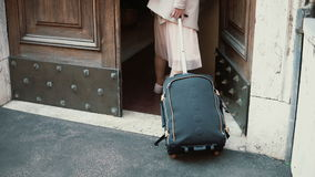 Jonge reizigersvrouw die met een koffer in de straat lopen Het meisje opent de deur en komt in een boog Royalty-vrije Stock Foto's