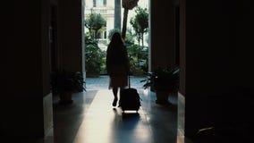 Jonge reizigersvrouw die met een koffer in de straat lopen Het meisje opent de deur en komt in een boog Royalty-vrije Stock Afbeeldingen