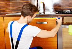 Jonge reparatiemens die keukenkast meten stock foto