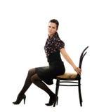 Jonge retro vrouwenzitting op rand van de stoel Stock Foto's