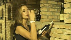 Jonge rode wijn van glas drinken en vrouw die fles in kelder kijken Vrouw die winemaker en het drinken rode wijn proeven stock video