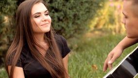 Jonge romantisch in aard speelt zijn meisje op gitaar stock footage