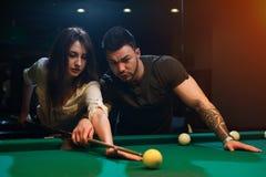 Jonge romantische paar het spelen snooker in club royalty-vrije stock afbeeldingen