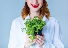 Jonge roodharigevrouw in de kruiden van de hoedenholding van orego stock foto