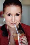 Jonge roodharigevrouw die vers jus d'orange drinken Royalty-vrije Stock Foto's