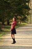 Jonge roodharigevrouw die zich op bosweg bevinden Stock Fotografie