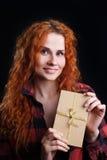 Jonge roodharigevrouw in geruite de giftdoos van de overhemdsholding op zwarte Stock Foto