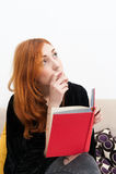 Jonge roodharigevrouw nadenkend met een boek Royalty-vrije Stock Afbeeldingen