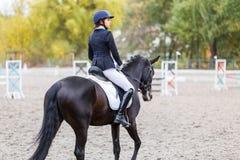 Jonge ruitervrouw op paard op de dressuurconcurrentie Royalty-vrije Stock Fotografie