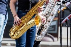 Jonge saxofonisten die saxofoons spelen tijdens straatprestaties stock foto
