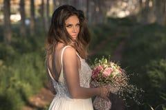 Jonge schitterende bruid die met perfecte huid en groene ogen een bruids boeket houden Stock Afbeelding