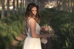 Jonge schitterende bruid die met perfecte huid en groene ogen een bruids boeket houden Royalty-vrije Stock Foto