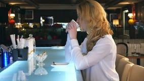 Jonge schitterende vrouwelijke het drinken koffie en zorgvuldig het kijken uit het venster van de koffiewinkel terwijl het geniet stock video