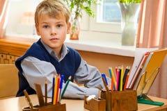Jonge schooljongenzitting achter een schoolbank Stock Foto