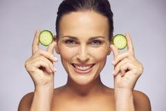 Jonge schoonheid die met komkommerplakken glimlachen Stock Foto