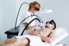 Jonge schoonheidsspecialist die torsohaar met een laser verwijderen aan haar cliënt in de schoonheidssalon Royalty-vrije Stock Foto