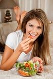 Jonge schoonheidsvrouw die salade eet Stock Afbeeldingen
