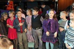 Jonge schouwburgbezoekers kinderen die enthousiast van het Kerstmispoppenspel van kinderen op het theater Smeshariki letten Stock Fotografie