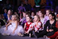 Jonge schouwburgbezoekers kinderen die enthousiast van het Kerstmispoppenspel van kinderen op het theater Smeshariki letten Royalty-vrije Stock Fotografie