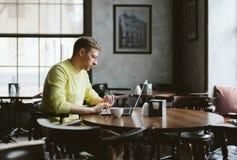 Jonge schrijver in een comfortabele koffie royalty-vrije stock afbeeldingen