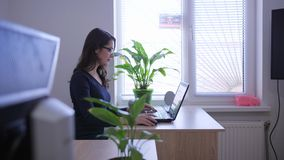 Jonge secretaressevrouw die bij laptop in bureau werken stock videobeelden