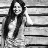 Jonge sensueel & de schoonheid die donkerbruine vrouw glimlachen stelt op houten achtergrond Royalty-vrije Stock Fotografie