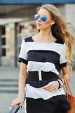 Jonge sensuele en mooie vrouw in een modieuze kleding met bedelaars Stock Foto