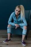 Jonge sexy blonde vrouw in blauw overhemd en jeans die als voorzitter zitten Stock Foto