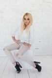 Jonge sexy blonde vrouw in witte overhemd en jeans en zwarte schoenen Royalty-vrije Stock Afbeeldingen