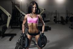 Jonge sexy geschiktheids donkerbruine vrouw in de gymnastiek die oefeningen doen Royalty-vrije Stock Foto