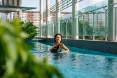 Jonge sexy Kaukasische vrouw die in zwempak op stadslandschap kijken van dak zwembad met groene bomen stock afbeeldingen