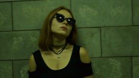 Jonge sexy modieuze Dame in glazen die zich dichtbij de muur bevinden stock video
