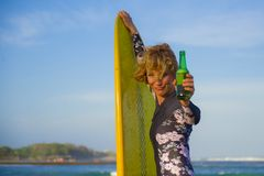 Jonge sexy mooie en gelukkige surfervrouw die gele brandingsraad houden die vrolijke het drinken bierfles glimlachen die de zomer stock fotografie