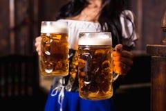 Jonge sexy Oktoberfest-serveerster, die een traditionele Beierse kleding dragen, die grote biermokken dienen bij bar stock afbeeldingen