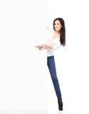 Jonge sexy vrouw die in denimjeans een lege banner geïsoleerd houden Stock Fotografie