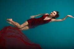 Jonge sexy vrouw die op zwembad in rood drijft Royalty-vrije Stock Afbeeldingen