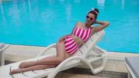 Jonge sexy vrouw in gestreept zwempak die door de pool liggen stock videobeelden