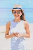 Jonge sexy vrouw met oortelefoons die telefoon op het strand met behulp van stock foto