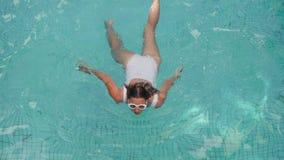 Jonge sexy vrouw in wit zwempak die in pool zwemmen stock videobeelden