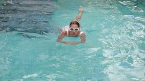 Jonge sexy vrouw in wit zwempak die in pool zwemmen stock footage