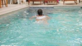 Jonge sexy vrouw in wit zwempak die in pool zwemmen stock video