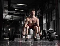 Jonge shirtless mens die deadlift oefening doen bij de gymnastiek Stock Foto