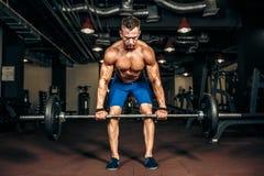 Jonge shirtless mens die deadlift oefening doen bij gymnastiek Royalty-vrije Stock Afbeelding