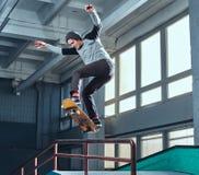 Jonge skateboarder die een truc op minihelling uitvoeren bij vleetpark binnen stock foto